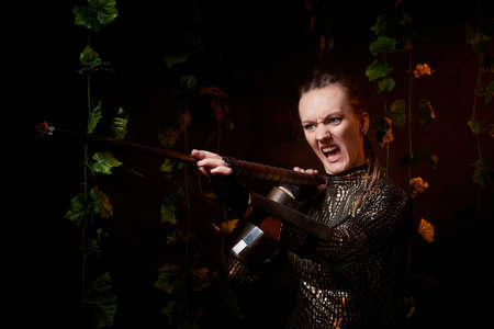 Valkyrie girl in shiny military armor and with a spear in a dark room with plants and vines. Model during a photo shoot, the actress during the shooting of the film 스톡 콘텐츠