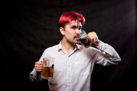 Young handsome guy with red hair in white shirt drinking beer. Funny man with emotions on the face and beer mug in hand and black background. Alcoholic is happy with alcohol. Model in studio