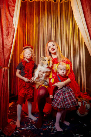 Family with dog during stylized theatrical circus photo shoot in a beautiful red location. Model mother and daughters with small animal posing on stage with curtain