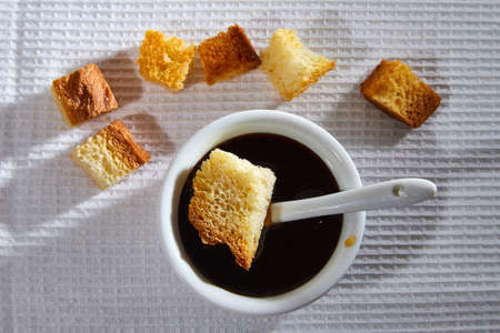 Liquid honey in a white plate and Square toasted pieces of homemade delicious rusk, hardtack, Dryasdust, zwieback on a white tablecloth Banco de Imagens