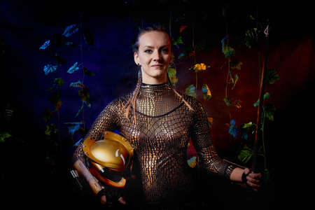 Valkyrie girl in shiny military armor and with a spear in a dark room with plants and vines. Model during a photo shoot, the actress during the shooting of the film