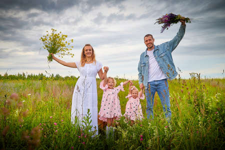 A family including two young parents and daughters on a walk in a meadow with grass and flowers. Dad, mom, girls relaxing and having fun in nature on a summer day with clouds Foto de archivo
