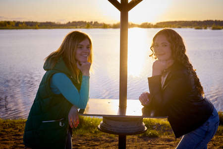 Two girls friends, sisters, cousins socializing and having fun near umbrella on the shore or beach of a lake or river with calm water and sunset in the background on the horizon.