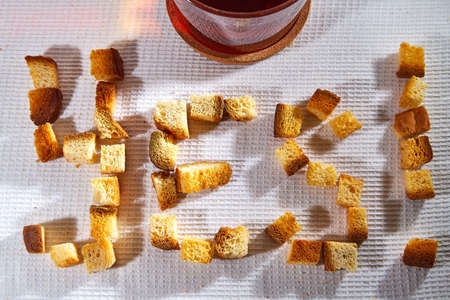 Word Yes made from Square toasted pieces of homemade delicious rusk, hardtack, Dryasdust, zwieback on a white tablecloth