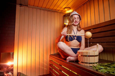 Beautiful girl with yellow broom on wooden bench at sauna in steam room with nice red and yellow light