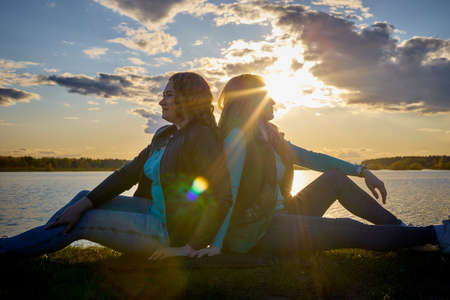 Two girls friends, sisters, cousins socializing and having fun on the shore or beach of a lake or river with calm water and sunset in the background on the horizon