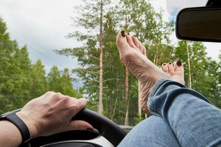 View of leg of woman lying on the dashboard of a car near the steering wheel and hand near it and the forest in the background behind the windshield.