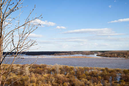 High water on a river or on a lake in sunny spring day. Russian nature landscape with water, trees and blue sky with white clouds Stock fotó