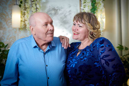 Portrait of an elderly bald man and fat plump woman in a blue dress in a nice room. Old pensioner father and adult daughtes posing during photoshoot in family holiday Imagens
