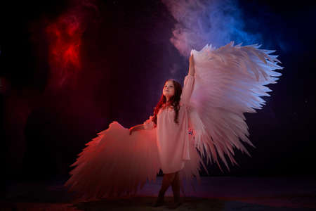 Small young model girl with white wings posing and dancing in dark black studo during photoshoot with flour or dust and color light. Actress in performance about struggle between good and evil