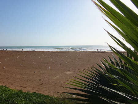 View from sand beach to water of sea and small waves in a nice day or evening with blues sky and bright sun. The concept of a holiday on the sea or ocean in the South Stock Photo