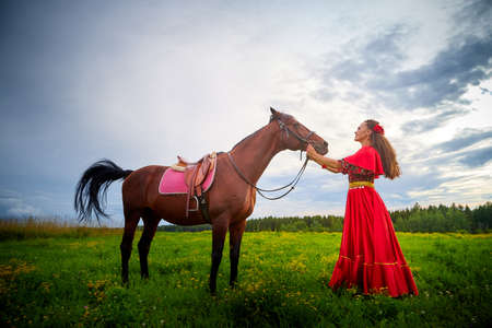Woman in a bright Gypsy dress and image with a horse in a field with green grass. A model or actress posing in nature with an animal from a farm and the sky with clouds in the background