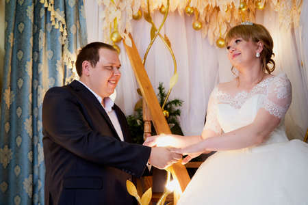 Bride and big fat groom together in a nice room in a wedding day