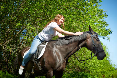 A fat girl and a brown horse in a Park on a Sunny day and green trees in the background. Young woman plus size rides a horse