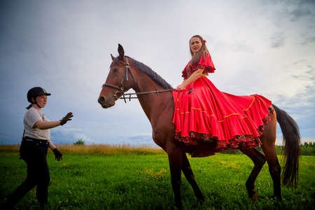 Kirov, Russia - August 01, 2020: Woman who is model or actress posing in red Gypsy dress with horse and trainer or groom in field with green grass and the sky with clouds in the background