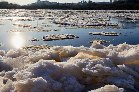 Ice drift on a river with blue high water and big water, white snow broken ice full of hummocks in it and sun reflection in sunny spring day Stockfoto - 155804268