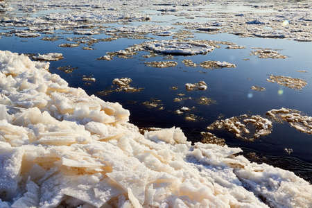 Ice drift on a river with blue high water and big water, white snow broken ice full of hummocks in it and sun reflection in sunny spring day Stockfoto