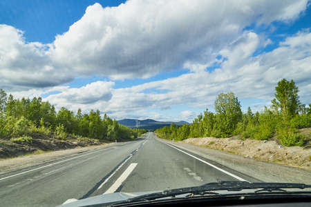 View from car window on the road and landscape with forest, tees, and blue sky with clouds. Landscape through windscreen with a relief. Trip for isolation in a coronavirus Stockfoto - 155804271