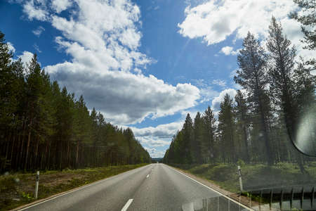 View from car window on the road and landscape with forest, tees, and blue sky with clouds. Landscape through windscreen with a relief. Trip for isolation in a coronavirus