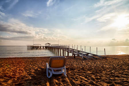 Sunbed on the sand beach and view to water of sea, pierce and blue sky with white clouds in a nice day, morning or evening. The concept of a holiday on the sea or ocean in the South