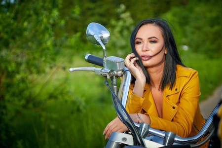 Attractive female brunette motorcyclist with motorcycle in a summer day. Beautiful girl with a bike. Adventure and travel concept Stockfoto