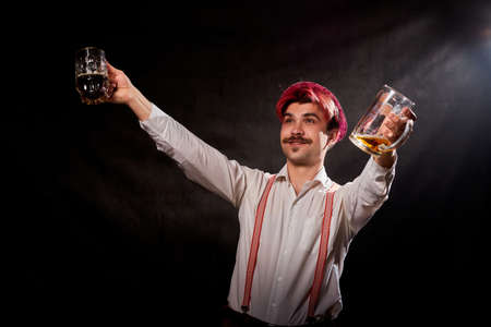Portrait of Oktoberfest funny young man or guy in traditional national ethnic clothes and hat with beer at studio with black background. Concept celebration of festival. Happy alcoholic with alcohol