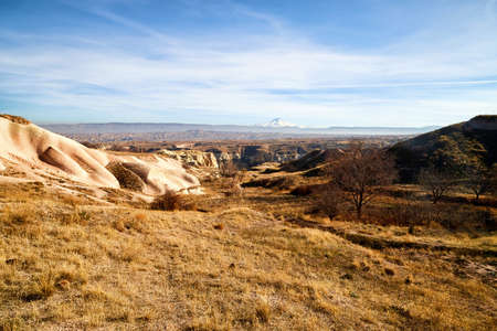 View of the landscape in the Cappadocia valley with strange yellow mountains, rocks and hills and blue sky background in a sunny day Stockfoto - 155804280