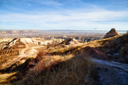 View of the landscape in the Cappadocia valley with strange yellow mountains, rocks and hills and blue sky background in a sunny day Stockfoto - 155804281