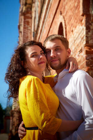 A date between a young girl and a guy on a Sunny summer day. Young beautiful couple on a walk in the city. Man and woman at a love meeting with hugs and kisses outdoors