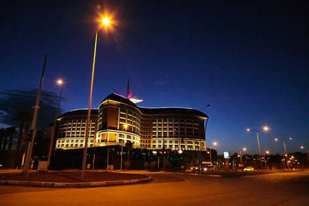 Antalya, Turkey - December 12, 2019: Beautiful building of hotel with nice illumination in an evening or night on the street of Lara in Antalya. The concept of rich and comfortable holiday in Turkey