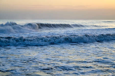 Water of sea with waves and yellow sky at sunset Stockfoto