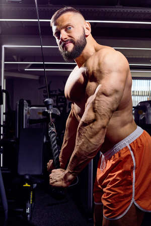 Handsome male bodybuilder in the gym. Big strong man during training in the gym. Guy with big muscles who is an athlete, trainer or instructor