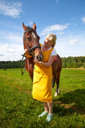 Girl in a yellow dress with a horse on a green field and a blue sky with white clouds on the background Stockfoto