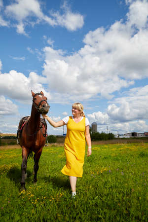 Girl in a yellow dress with a horse on a green field and a blue sky with white clouds on the background Stockfoto - 155840169