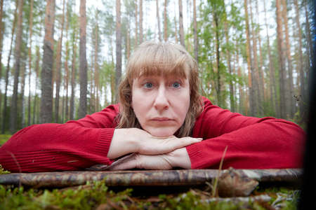Middle-aged woman lies on a Mat in the forest in a spring or autumn day. Rest on nature alone Stockfoto - 155840172