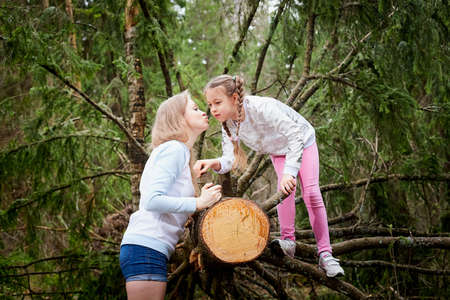 Mother and her child girl playing and having fun together on walk in forest outdoors. Happy loving family posing on nature landscape with with pine trees