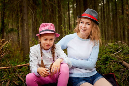 Mother and her child girl playing and having fun together on walk in forest outdoors. Happy loving family posing on nature landscape with with pine trees Stockfoto - 155933045