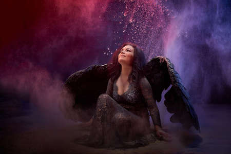 Girl in black dress and with black wings posing in dark studo during photoshoot with flour or dust and light. A fallen angel begs and asks for something during global struggle between good and evil Stockfoto