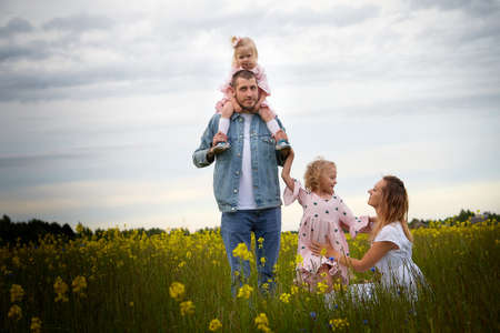 Family including two young parents and daughters on a walk in a meadow with grass and flowers. Dad, mom, girls relaxing and having fun in nature on a summer day with clouds
