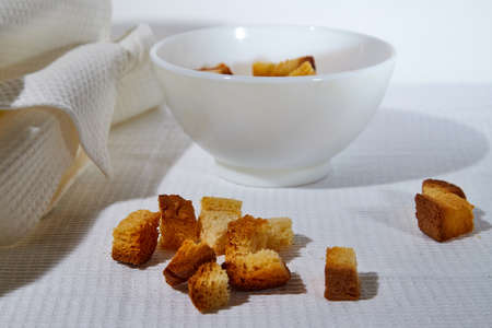 Square toasted pieces of homemade delicious rusk, hardtack, Dryasdust, zwieback in a plate on a white tablecloth Stockfoto - 155933239