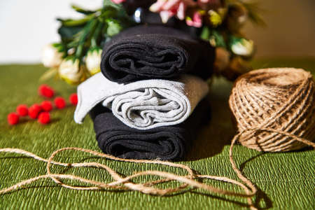 Several pairs of new male cotton socks on a green surface, skein of thread and flowers background. The concept of coziness and comfort. Gift to a man and taking care of him