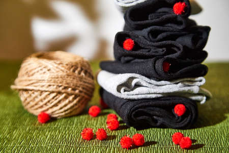 Several pairs of new male cotton socks on a green surface and skein of thread. The concept of coziness and comfort. Gift to a man and taking care of him Stockfoto