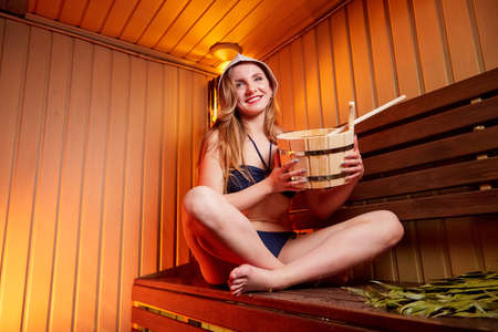 Beautiful girl on wooden bench in steam room with nice light