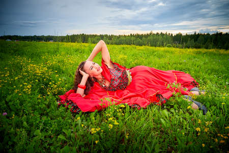 A woman in a bright red dress that looks like a Gypsy carnival costume is lying on green grass in a field