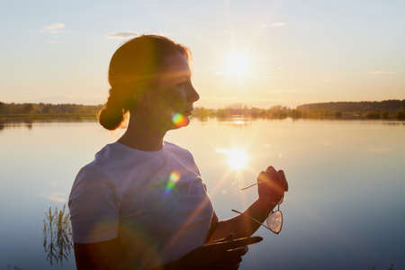 Portrait of the girl or woman on the shore or beach of the lake in the evening at sunset. Sun other water Stockfoto