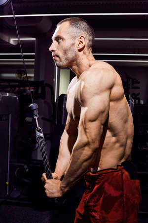 Handsome young male bodybuilder in the gym. Big strong man during training in the gym. Guy with big muscles who is an athlete, trainer or instructor Standard-Bild