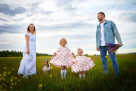 Family including two young parents and daughters on a walk in a meadow with grass and flowers. Dad, mom, girls relaxing and having fun in nature on a summer day with clouds Foto de archivo
