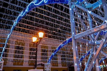 Decorated Christmas tunnel with lights in background in the night street of the city. Background for photoshoot