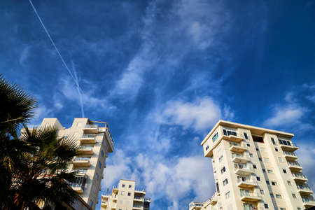 Beautiful white clouds in blue sky over city houses.