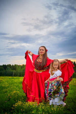 Mother and daughter in colorful dresses similar to Gypsy resting and having fun in meadow with green grass. Models an adult woman and little girl posing or performing in field in evening with clouds